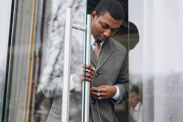 Empresário americano africano em terno cinza clássico, deixando o prédio de escritórios