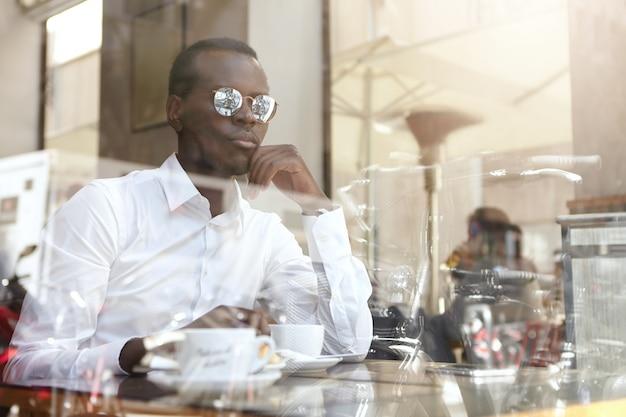 Empresário americano africano moderno sério tomando café no café, sentado à mesa com caneca e olhando através do vidro da janela do lado de fora, segurando a mão no queixo com expressão pensativa e pensativa