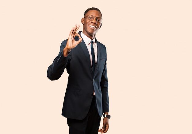 Empresário americano africano, sentindo-se feliz, relaxado e satisfeito, mostrando aprovação com gesto bem, sorrindo contra parede bege