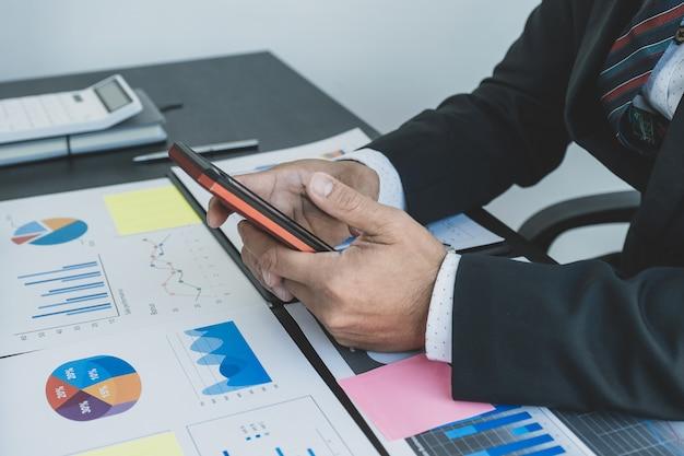 Empresário analisa o gráfico de finanças com smartphone no escritório para definir metas de negócios de gerenciamento desafiadoras e planejar para atingir a nova meta.