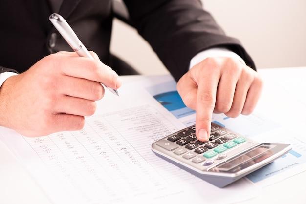 Empresário analisando contas, investimentos e gráficos com calculadora na mesa