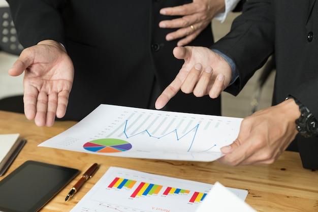 Empresário, analisando e discutindo com tablet e papelada documento