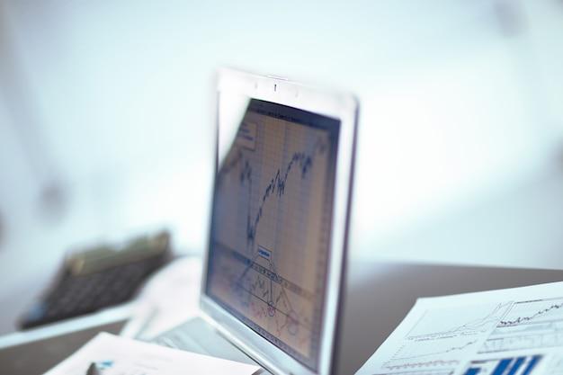 Empresário analisando gráficos de investimento com o laptop.