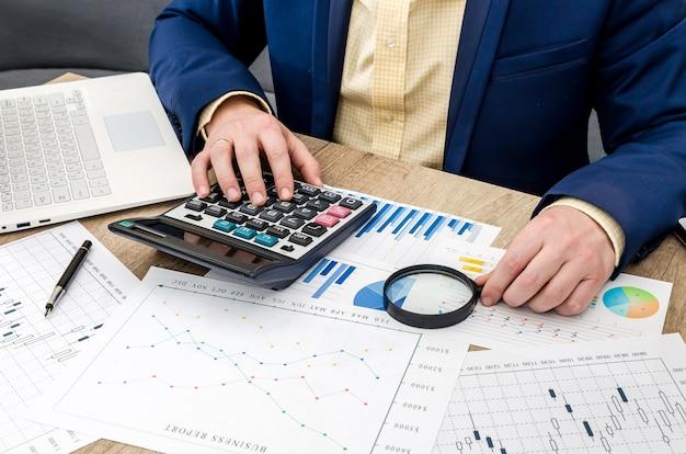 Empresário analisando gráficos de negócios com lupa