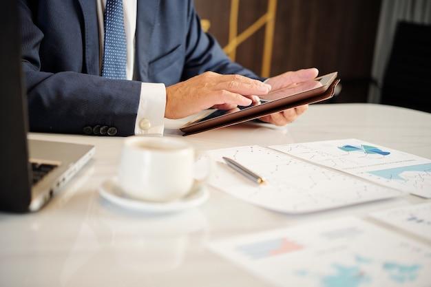 Empresário analisando gráficos financeiros e verificando e-mails importantes no tablet enquanto toma um café