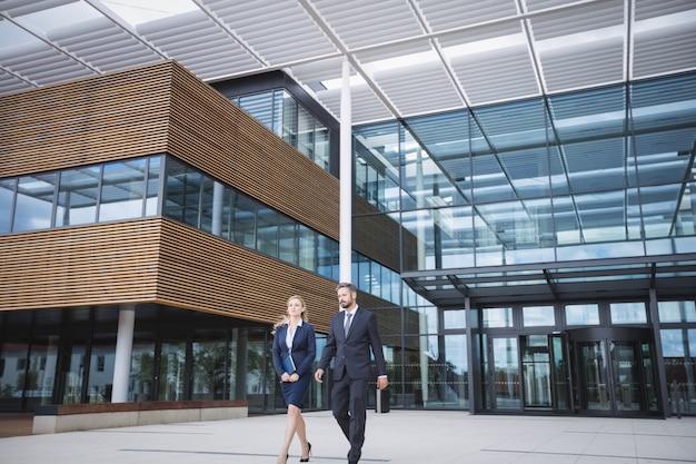 Empresário andando com colega fora do prédio de escritórios
