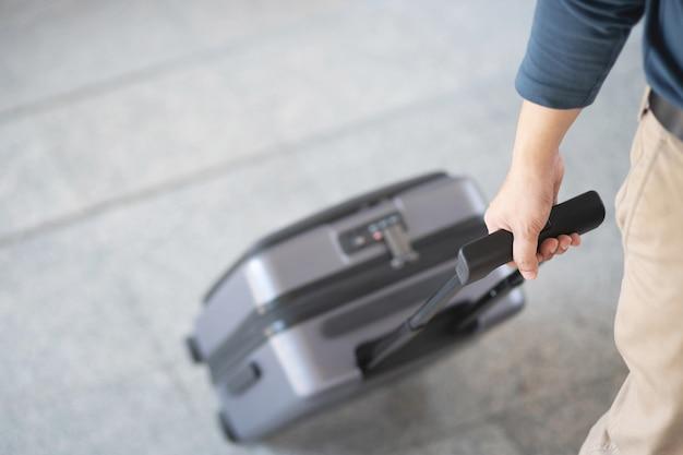 Empresário andando do lado de fora do prédio de transportes públicos com bagagem na hora do rush. viajante de negócios puxando a mala no moderno terminal do aeroporto. viagem de negócios de bagagem.