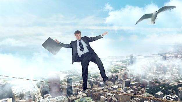 Empresário andando em uma corda sobre o centro de negócios. risco de falência, conceito de equilíbrio financeiro