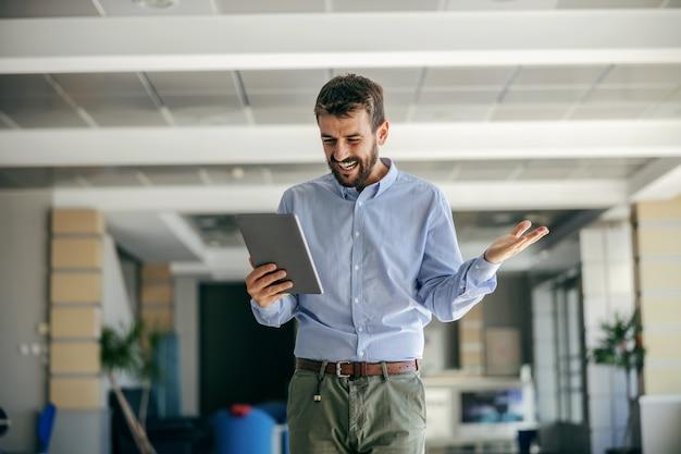 Empresário andando no corredor de sua empresa e segurando o tablet.