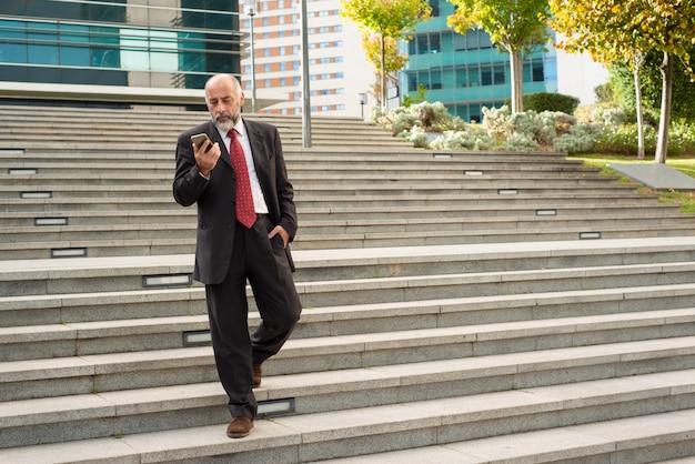 Empresário andando nos degraus e usando smartphone