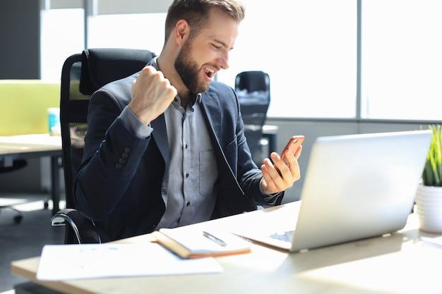 Empresário animado lendo boa mensagem em seu celular no escritório.