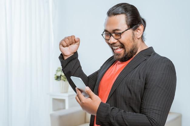Empresário animado levanta o gesto de sucesso do braço com telefone