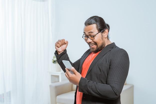 Empresário animado levantou o gesto de sucesso do braço com telefone