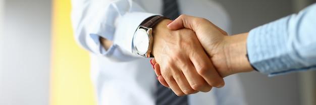 Empresário aperta a mão de uma mulher em close up do escritório.
