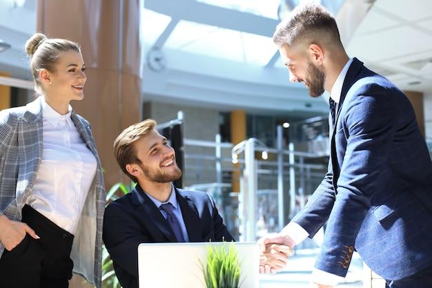 Empresário apertando as mãos para selar um acordo com seu parceiro e colegas de escritório.