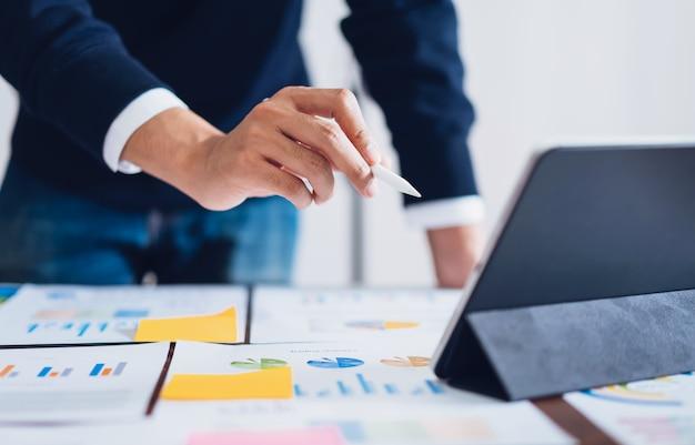 Empresário, apontando canetas digitais para tablet e trabalhando na mesa e documentos financeiros no escritório.