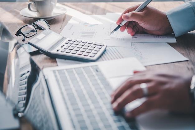 Empresário, apontando com uma caneta no gráfico de relatório de negócios, está trabalhando em contas em análise de negócios com gráficos e documentação.