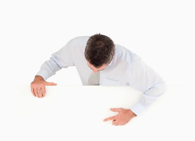 Empresário apontando para algo em um painel em branco