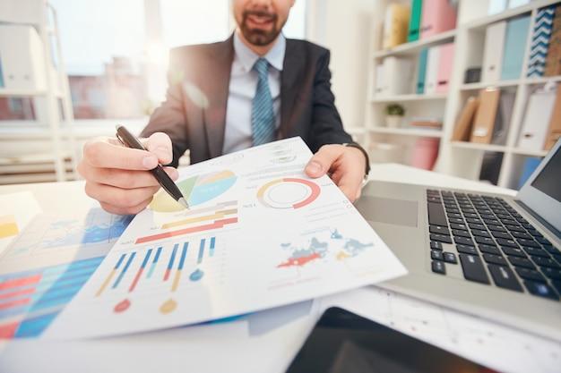 Empresário, apontando para o closeup de dados estatísticos