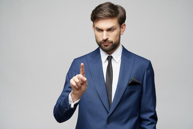 Empresário apontar o dedo na tela invisível, pressionando o botão virtual digital sobre parede cinza