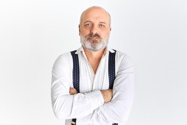 Empresário aposentado caucasiano sério vestindo camisa branca e suspensórios, olhando para a câmera com expressão facial confiante, cruzando os braços sobre o peito