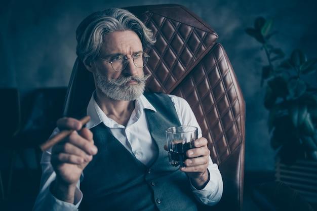 Empresário aposentado fuma charuto e bebida uísque em escritório cinza