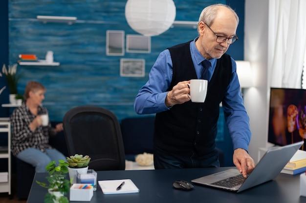 Empresário aposentado ligando o laptop e tomando uma xícara de café