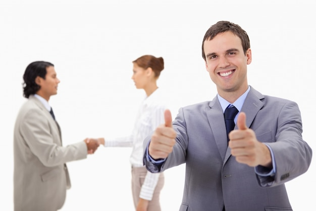Empresário aprovando com mão tremendo colegas atrás dele