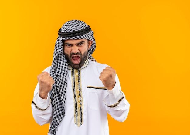 Empresário árabe com roupa tradicional e cara de raiva cerrando os punhos em pé sobre a parede laranja
