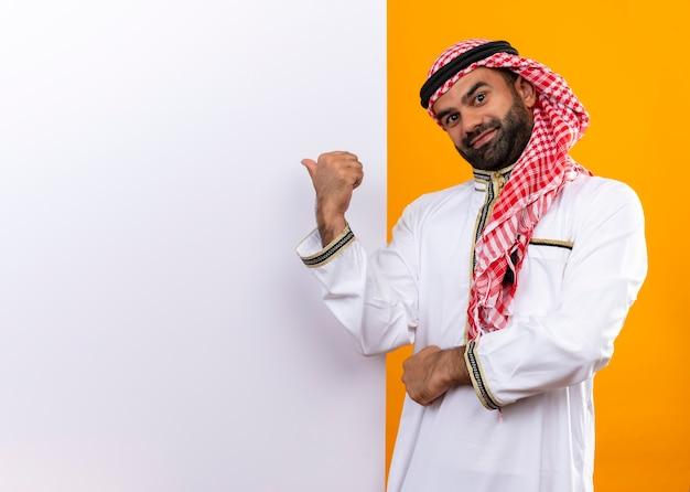 Empresário árabe com roupa tradicional em pé perto de um outdoor em branco apontando com o dedo para ele com um sorriso confiante no rosto sobre a parede laranja