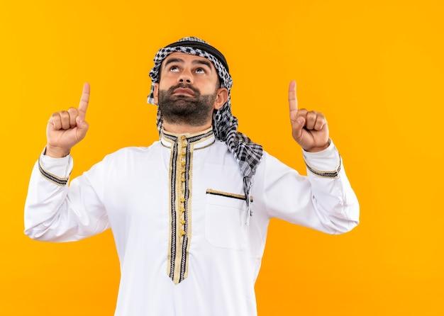 Empresário árabe com roupa tradicional, olhando para cima com uma cara séria apontando com os dedos em pé sobre a parede laranja