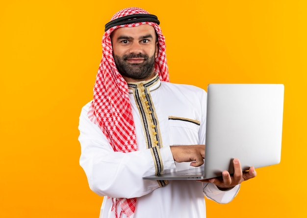 Empresário árabe com roupa tradicional segurando laptop com um sorriso no rosto em pé sobre uma parede laranja