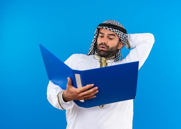 Empresário árabe com roupa tradicional segurando uma pasta aberta olhando para ele confuso em pé sobre a parede azul