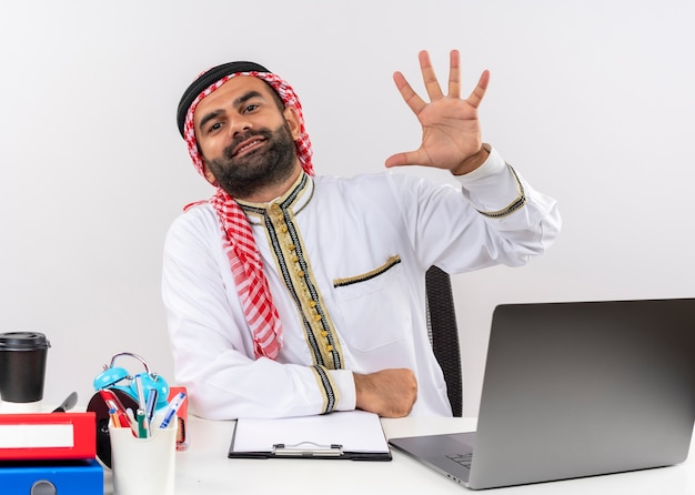 Empresário árabe com roupa tradicional sentado à mesa com o computador portátil aparecendo e apontando para cima com os dedos número cinco, sorrindo, trabalhando no escritório
