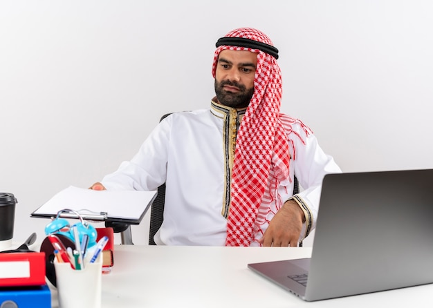 Empresário árabe com roupa tradicional sentado à mesa com um computador portátil segurando uma prancheta com páginas em branco, trabalhando no escritório