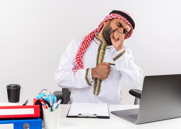 Empresário árabe com roupa tradicional sentado à mesa com um laptop, parecendo cansado, bocejando, trabalhando no escritório