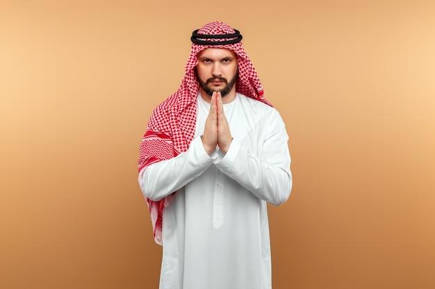Empresário árabe com roupas nacionais cruzou as mãos em oração, tipo, parede bege.