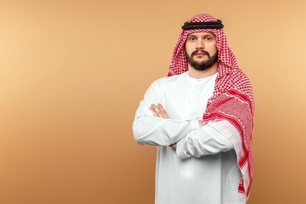 Empresário árabe com roupas nacionais cruzou os braços sobre o peito, parede bege.