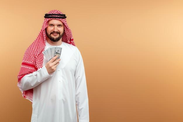 Empresário árabe com roupas nacionais está segurando dólares nas mãos.