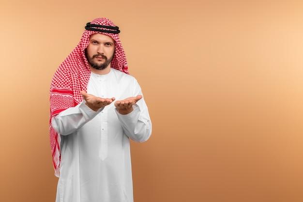 Empresário árabe com roupas nacionais exibe algo, parede bege.
