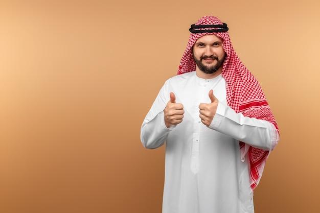Empresário árabe com roupas nacionais mostra polegares para cima, tipo, parede bege.