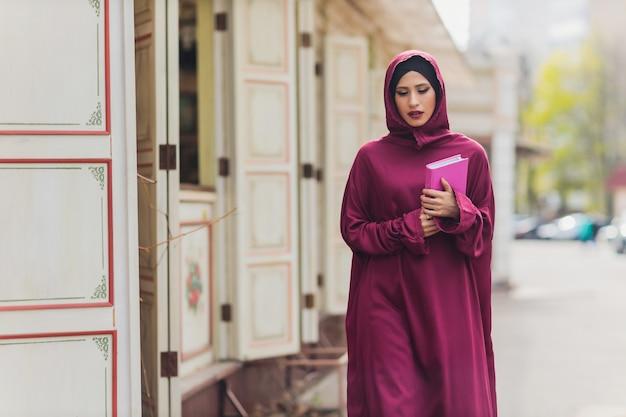 Empresário árabe confiante sorrindo e caminhando em dubai árabe negócios vumen hijab está nas ruas contra os arranha-céus de dubai a mulher está vestida com uma abaya preta