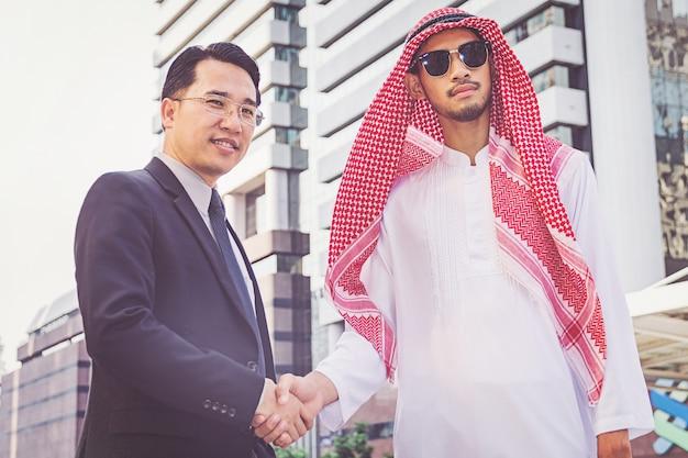 Empresário árabe dando um aperto de mão ao seu parceiro de negócios, no canteiro de obras