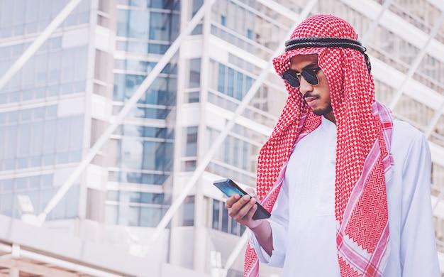 Empresário árabe de mensagens em um telefone celular na cidade