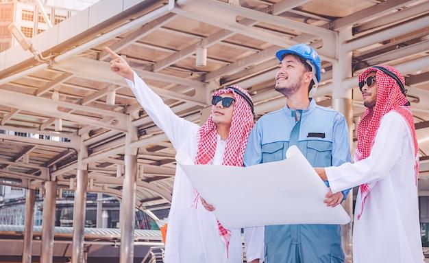Empresário árabe e engenheiro reunião projeto no canteiro de obras