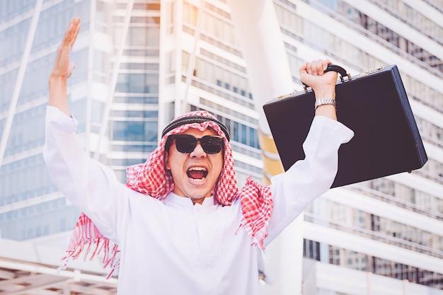 Empresário árabe em pé por levantar as duas mãos na cidade