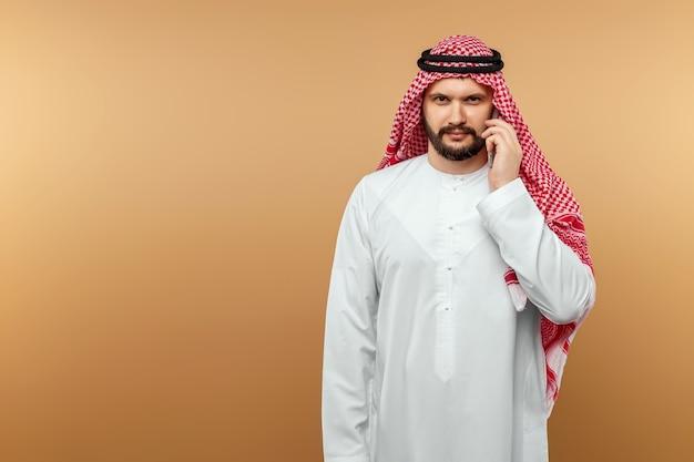 Empresário árabe em roupas nacionais, falando em um smartphone, tipo, parede bege.
