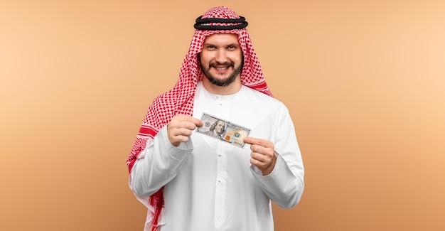 Empresário árabe em roupas nacionais se alegra em dólares em suas mãos, grande lucro.