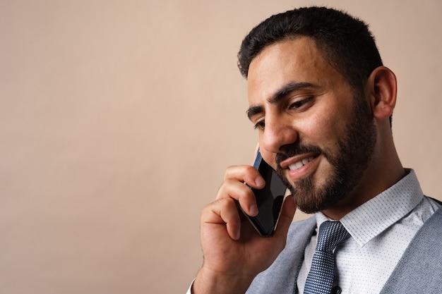 Empresário árabe falando ao celular contra um fundo bege