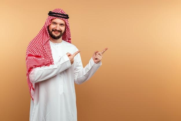 Empresário árabe masculino com roupas nacionais aponta com as mãos para algo, parede bege.